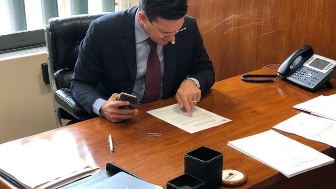 João Roma em uma mesa lendo um documento
